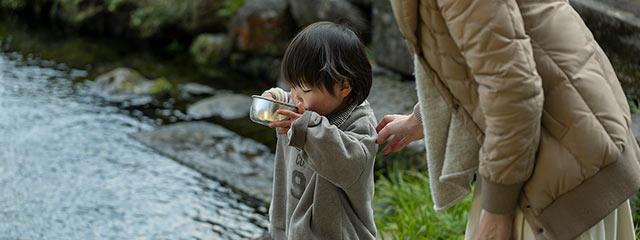 湧水を飲むさくらさんの息子さん