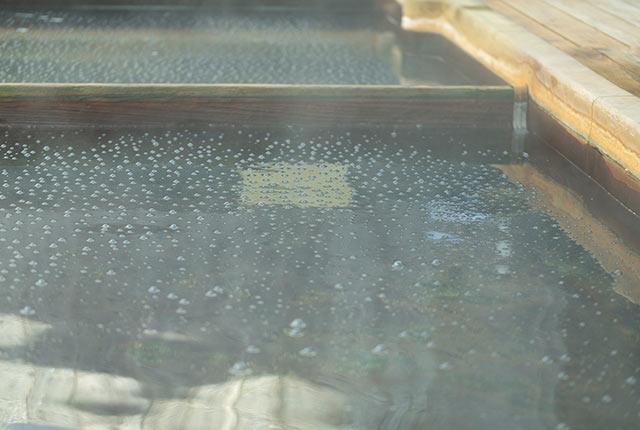 温泉の表面に炭酸泡が浮かぶ